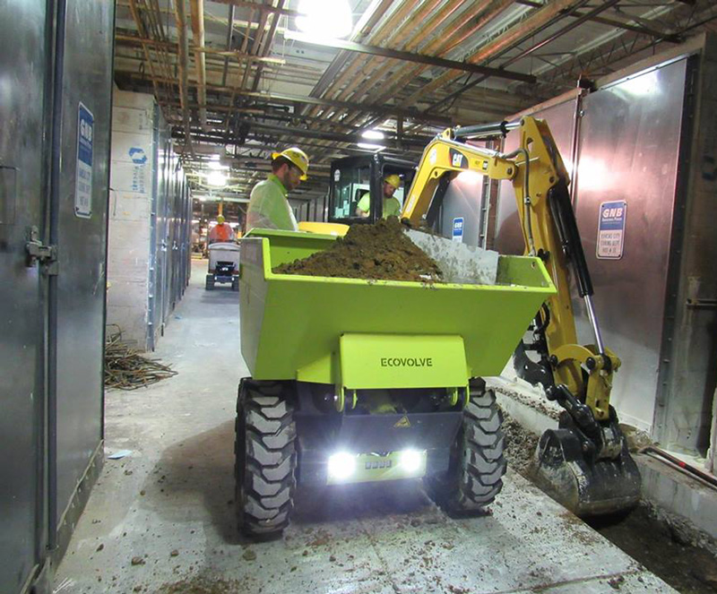 Ecovolve Electric skip loading dumper being loaded by a hybrid digger