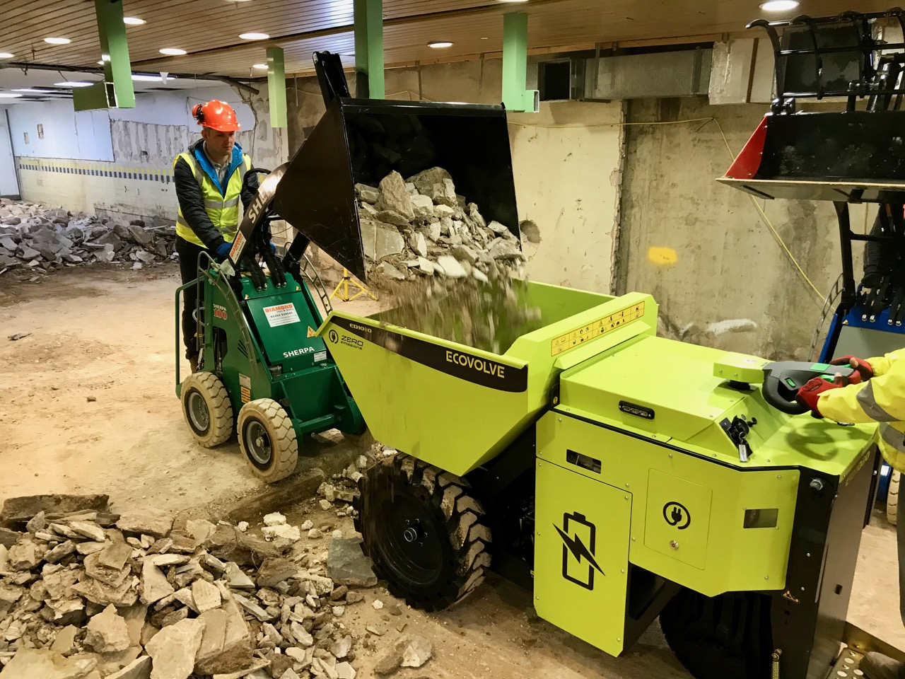 Ecovolve Electric Dumper being loaded by a Sherpa Electric Mini loader on a demolition site